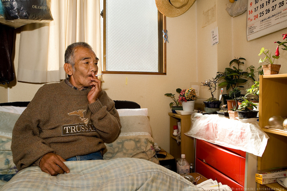 Tomikazu Maeno pentioner and ex day laborer in the room he rents at the Senior House Hidamari, in Airin. Before he became a day laborer, he used to be a Yuzen Kimono painter. He also has a history of having killed one person when he was young..The old name of the area now called Airin, was untill 1966 Kamagasaki and many people still call it like that. .Kamagasaki (????) is an old place name for a part of Nishinari-ku in Osaka, Japan. Airin-chiku (???????) became the region's official name in May, 1966.Sections of four different towns: Nishinari-ku Taishi (??????), Haginochaya (?????), Sanou (???), North Hanazono (????) and Tengachaya (?????) are collectively known as the Kamagasaki region..Kamagasaki as a place name existed until 1922. Kamagasaki is known as Japan's largest slum, and has the largest day laborer concentration in the entire country. 30,000 people are estimated to live in every 2,000 meter radius within this region. An accurate count of occupants has never been produced, even in the national census, due to the large population of day laborers who lack permanent addresses..