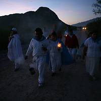 Followers of Nino Fidencio, a curandero or healer who passed away in the 1938, walk through the desert to an early morning prayer and healing session on top of a hill just outside of Espinazo, Mexico on October 18, 2006. Followers of Nino Fidencio believe that his spirit can posses other healers, who once possessed speak in a child like voice and perform a variety of medical cures on their followers. His believers, an estimated 20,000, gather in his hometown for a three-day festival twice a year in March and October. (Photo/Scott Dalton)