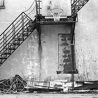Basketball hoop in alleyway.