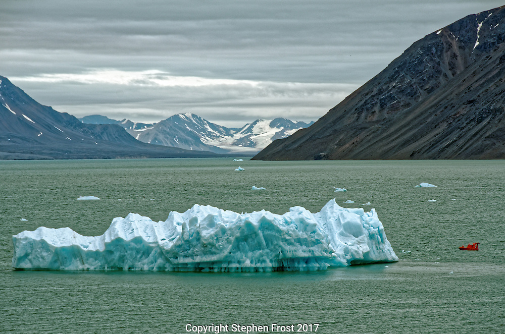A lifeboat inspects an iceberg in the Arctic ocean off Svalbard.<br />