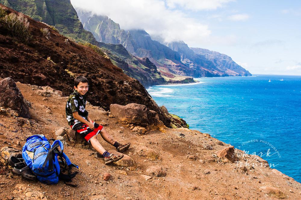 Boy resting on the Kalalau Trail, Na Pali Coast, Kauai, Hawaii