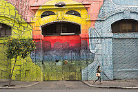 A woman walks past a colorfully painted building in Rome