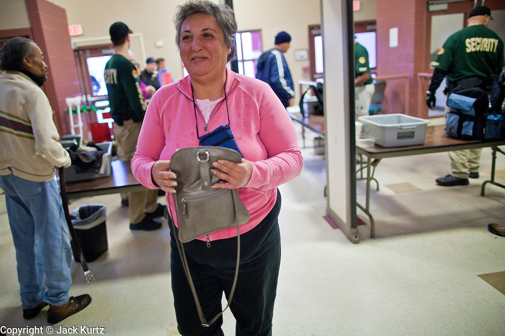 "29 DECEMBER 2010 - PHOENIX, AZ: MIRELLA, a homeless woman, goes through security while checking in for the night at Central Arizona Shelter Services (CASS) in downtown Phoenix Wednesday. Phoenix was hit by a winter storm Wednesday that brought heavy rain and unusually cold temperatures, it is the first day of what is expected to be a week of below normal temperatures. Morning lows by Friday are expected to be 15-20 degrees blow normal. Normal lows for Phoenix are in the 40's but by Friday are expected to be in the 20's. A spokesman for CASS said they expected to fill all of their regular shelter spaces and most of their overflow spaces every night for the next week. In addition to the cold weather CASS has seen demand for the services increase sixfold in the last three years as the Phoenix economy has slid into recession. Many CASS clients now are the ""new"" homeless - people who used to have homes but lost their homes in the bad economy.      PHOTO BY JACK KURTZ"