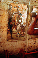 """KOLHAPUR, INDIA - MARCH 22: Indian men practice the three thousand year old sport known as """"Kushti"""", a form of wrestling, in its traditional form at the fight club Shahupuri in Kolhapur, India.  In this south-eastern Indian city Kushti has a long tradition. It used to be supported by local maharajas and is financed by the government. But its days are numbered. Last year, the Indian Fighters Federation in the capital of New Delhi stunned thousands of fighters when it announced prohibition of fighting on red soil and ordered fight clubs to buy mattresses for their arenas. Ending the traditional red clay wrestling was an idea sprouted from the aspiration to achieve more Olympic medals since the last and only medal India brought home in wrestling was a bronze in 1952. So far no one here in Kolhapur is buying the mattresses and instead they continue the rigorous schedule of waking up at 3:30am six times a week and practicing more than 6 hours every day. They live together in one small room above the arena and their only belongings are a blanket, a few items of clothes and some books about the art of Kushti. They have been compared to holy men because of their celibacy and dedication and they practice exercises like standing on one's head for lengths of time to expel """"filthy"""" thoughts. (Photo by Ami Vitale)"""
