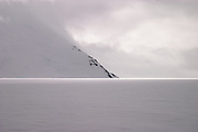 A sliver of light illuminates the horizon below a mountain during a storm. British mountaineering expedition to Knud Rasmussens Land, East Greenland, Arctic, 2006.
