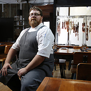 SHOT 8/15/13 4:24:13 PM - Justin Brunson, Owner and Executive Chef at Old Major restaurant in Denver, Co. Includes images of menu items : The Nose to Tail Plate : confit rib, pork chop, crispy belly, city ham, crispy ear, Denver Bacon Co. barbecue beans, cole slaw and corn bread $29 and Pan Seared Scallops : baby vegetables, fregola, spinach purée, toasted pine nuts, roasted garlic vinaigrette $27. The restaurant focuses on heritage-raised meats from Colorado farms, features an in-house butchery program and bills itself as contemporary farmhouse cuisine. (Photo by Marc Piscotty / © 2013)