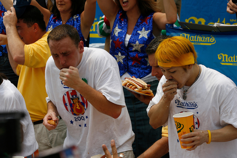 NEW YORK, NY-06 JUL04-- Takeru Kobayashi and American favourite Joey Chestnut neck-in-neck during the hot dog eating competition (Extra) The Gazette/Liam Maloney