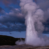 Old Faithful Geyser erupts at twilight, autumn of 2015.