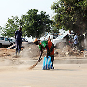 A woman cleans omnipresent dust off of the streets in Juba's old town in preparation for the Independence ceremonies on July 9th.
