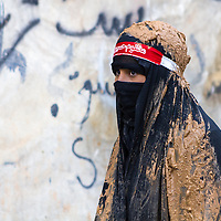 A young shiite muslim girl, covered in mud, mourning during the Day of Ashura in Bijar, Iran.
