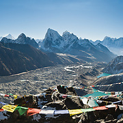 Hike up 2000 feet from Gokyo village to the peak of Gokyo Ri (17,575 feet / 5357 meters elevation) for a spectacular panorama of mountains, glaciers, and lakes in Sagarmatha National Park, in the Khumbu region of Nepal, Asia. Left of center on the horizon is Mount Everest, the highest peak on earth. Along the valley floor flows the gray rock-covered Ngozumpa Glacier, the largest in Nepal. A side (lateral) moraine dams several Gokyo Lakes. Prayer flags mark summit ridges. Sagarmatha National Park was created in 1976 and honored as a UNESCO World Heritage Site in 1979. (Panorama stitched from 5 images.)