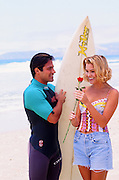 surfer and a beautiful blonde girl with a red rose at the beach in California