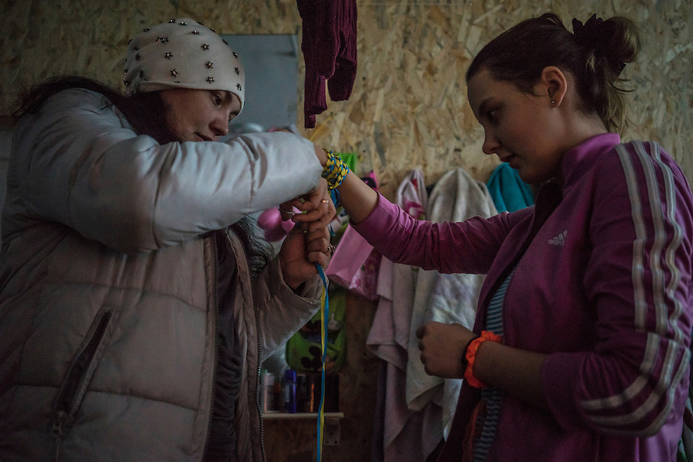 Natasha Kaporina, 37, left, cuts extra ribbon on her daughter's patriotic Ukraine-themed bracelet at Romashka, a summer camp where they and several hundred other people live after being displaced by fighting in Eastern Ukraine on Friday, February 13, 2015 in Kharkiv, Ukraine.