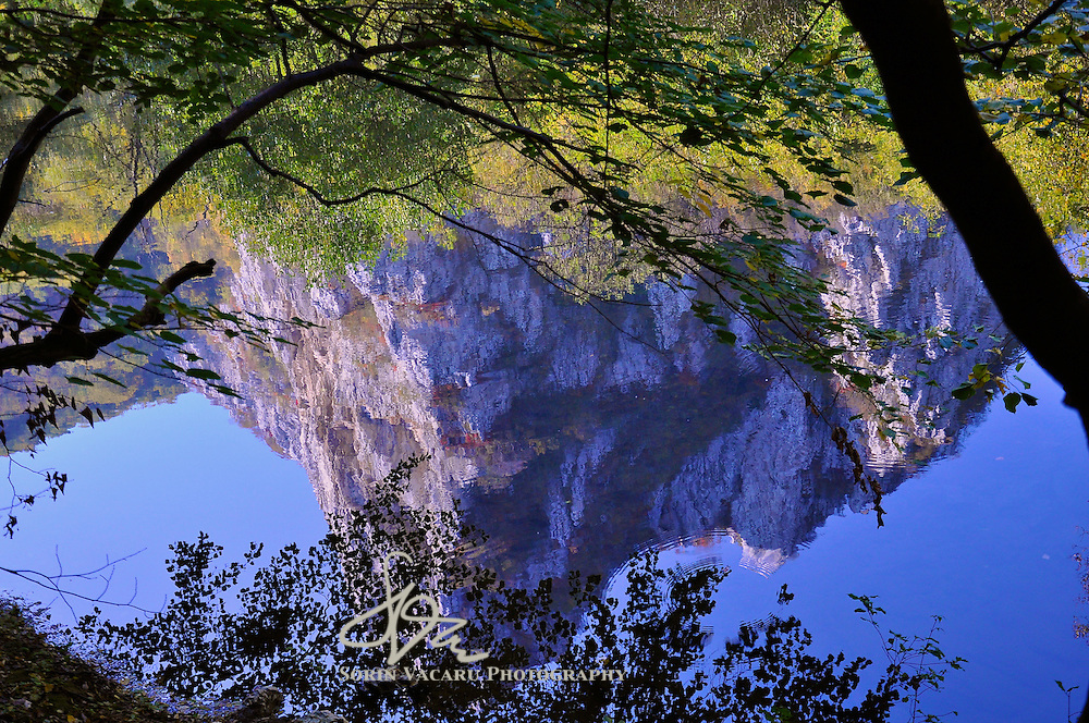 The limestone walls of the Nera River Gorge reflected in the tranquil waters.