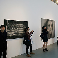 Beijing, April,2, 2011 : visitors take pictures in the hall with work by Chinese artists ( on the left).