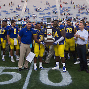 Delaware captains Running Back ANDREW PIERCE (30) and Defensive tackle ZACH KERR (94) receive The First State Cup from Delaware Gov. Jack Markell (Center) after defeating interstate State rival Delaware State University 42-21 Saturday. Sept Sept. 07, 2013 in Newark Delaware.<br />