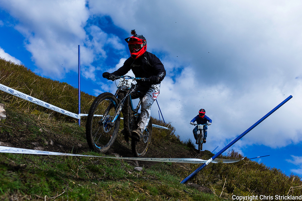 Ae Forest, Dumfries, Scotland, UK. 25th April 2015. Downhill Mountain Bikers Gregor Notman (51) & Christopher Whitfield both of All Terrain Cycles take on the 7Stanes course at Ae during the Scottish Downhill Association racing.