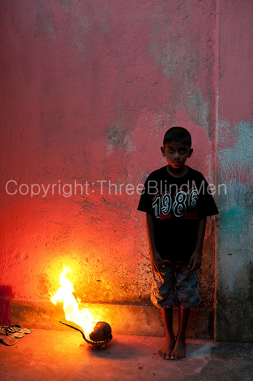 Young by at dusk by a brazier with coconut shells. At dusk, many of the houses will burn incencse in and around their homes.