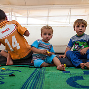 Brothers Ibrahim, 7, Adnan, 18 months, and Amir, 5, in their tent. Zaatari Camp for Syrian Refugees, Jordan, August 2013.