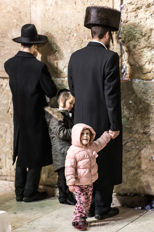 On a saturday evening a Haredi father takes his son and daughter to the Kotel who waits while he prays for Havdalah the end of Shabbet. Haredi lifestyle is family-centred. Boys and girls attend separate religious schools and proceed to higher Torah study in a yeshiva or seminary respectively.