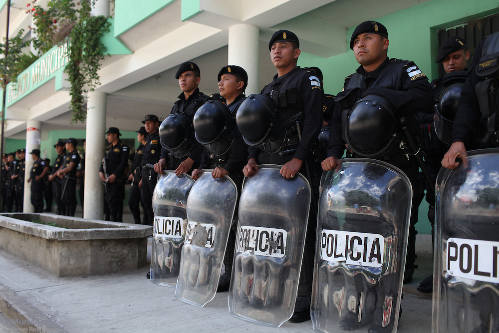 Riot police setup nearby as hundreds gather in the main square of San Rafael Las Flores, Guatemala, to demand that a community plebiscite on industrial mining be carried out in the municipality. The San Rafael Mine, 60% owned by US-based Tahoe Resources and 40% by Canadian mining giant Goldcorp, has been operating since 2011 without having previously consulted the local residents - a violation to numerous international conventions. San Rafael Las Flores, Santa Rosa, Guatemala. July 20, 2012.