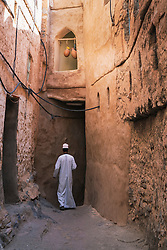Man walking in alleyway of old traditional village of Misfat al Abryeen in Oman Middle East