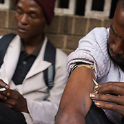 "Sfiso, a drug addict, using a visibly dirty shared needle to inject himslef with ""nyaope"" on a street in Hillbrow, an inner-city neighbourhood in Johannesburg, South Africa that is plagued by drugs. A crude form of heroin reputedly cut with anything from anti-retrovirals to rat poison to pool cleaner, nyaope is cheap (about R20/ $1.70 per ""round"") and devastatingly addictive - it produces a brief high, but then leaves the user with vicious withdrawal symptoms, constantly searching for the next high. It is said that a single dose is enough to result in addiction."