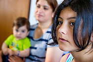 Liza, a Yazidi refugee from northern Iraq, sits with her family in one of the two rooms they share in an asylum center in a small Bavarian town near the Austrian border on June 5, 2015 in Neukirchen vorm Wald, Germany. As a part of the local push to integrate recent refugees, Liza will begin learning German in a local school. Ann Hermes/© The Christian Science Monitor 2015