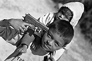 A child and his brother play with a toy gun in a park near Pokhara