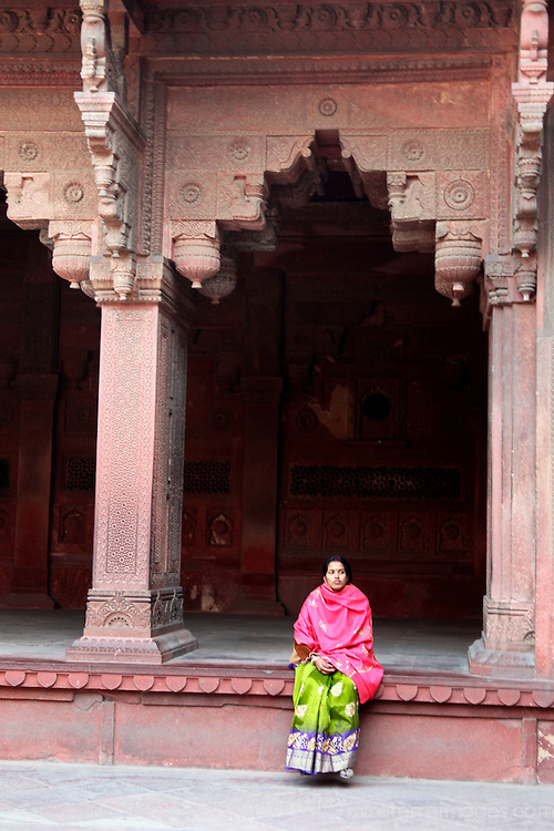 Asia, India, Agra. Woman sitting at the Red Fort of Agra, a UNESCO World Heritage Site.