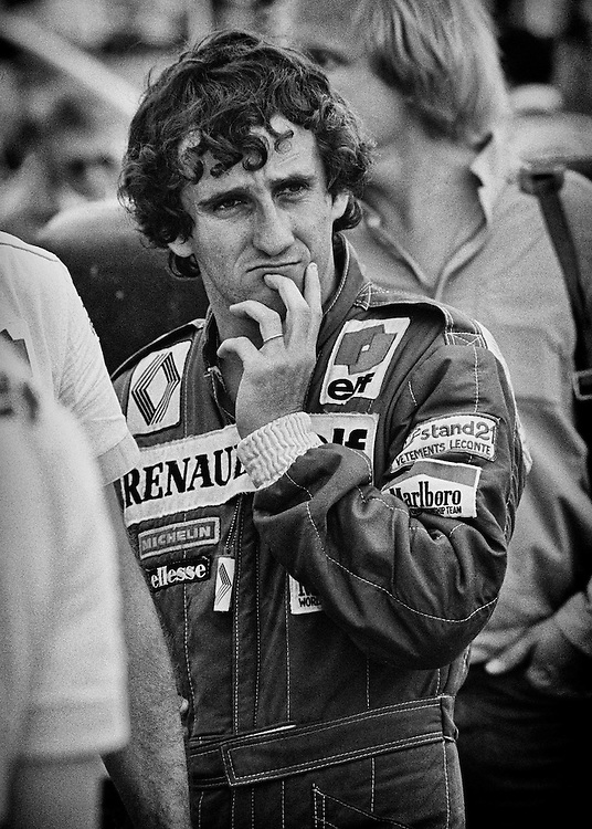 French driver Alain Prost contemplates changes to his Renault RE30B before qualifying for the 1982 Detroit Grand Prix.  He would go on to qualify on the pole and lead the race until electronic ignition problems would have him fall down the order to 11th at the finish. Prost had won the first two Grands Prix of the season, but then had three retirements and was desperate to ease team pressure and return to form. <br /> <br /> Prost would have a public feud with teammate Rene Arnoux later that year following the French Grand Prix, by feeling that Arnoux went refused team orders to let Prost pass him for the victory. It turned many French fans against him. By 1984, Prost had also left Renault for Marlboro McLaren, having never won the World Champonship for the french auto giant. <br /> <br /> He would enjoy his best years with Team McLaren, winning three World Championships (1985,1986,1989), with a fourth added in 1993 with Williams.