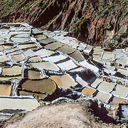 "Since pre-Inca times, salt farmers at the saltworks (salinas) near Maras have evaporated salty water from a subterranean stream in Peru, South America. A rough dirt road connects Maras (in the Urubamba/Vilcanota River Valley, Sacred Valley of the Incas) with Cuzco (40 km north) and other towns. The cooperative system of pond farmers was established during the time of the Incas, if not earlier, and is traditionally available to any person wishing to harvest salt. Intricate channels redirect water flow through several hundred ancient terraced ponds. As water evaporates from the sun-warmed ponds, it becomes supersaturated and salt precipitates as crystals. A pond keeper closes the water-feeder notch, allows the pond to go dry, then scrapes and carries away the dry salt. Salt color varies from white to a light reddish or brownish tan, depending on ""farmer"" skills. Panorama was stitched from 5 overlapping photos."