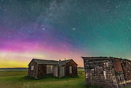 A dim aurora to the north at Grasslands National Park, Saskatchewan, at the Larson Ranch site and its rustic pioneer cabins. Taken August 8, 2016. This is looking northeast to Andromeda (the Andromeda Galaxy is above centre) and Perseus (the Double Cluster is left of centre). This Park is a Dark Sky Preserve. There are no lights visible. Illumination here is from starlight and the setting waxing crescent Moon to the southwest. <br /> <br /> This is a single exposure, 30 seconds untracked, with the Sigma 20mm lens at f/2 and Nikon D750 at ISO 3200, taken at the start of a time-lapse sequence. I cloned out the No Trespassing signs on the buildings.