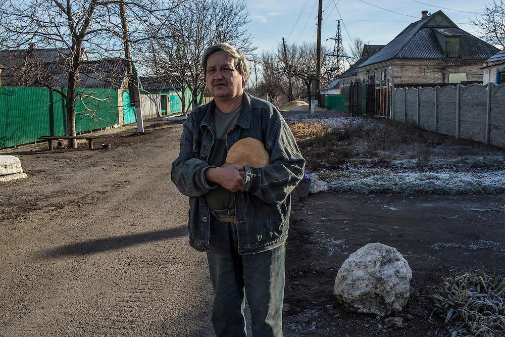 A local resident holds a loaf of free bread delivered by the Good Word Protestant Church in need on Thursday, December 10, 2015 in Mariinka, Ukraine.