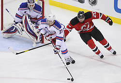 May 21, 2012; Newark, NJ, USA; New York Rangers defenseman Ryan McDonagh (27) skates with the puck while being defended by New Jersey Devils center Ryan Carter (20) during the second period in game four of the 2012 Eastern Conference Finals at the Prudential Center.