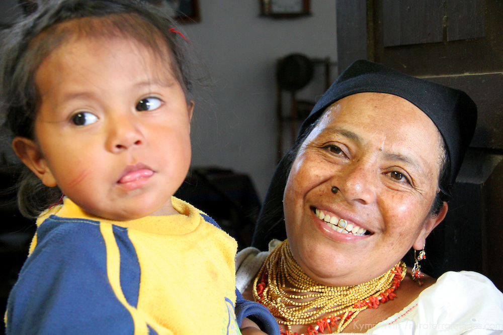 South America, Ecuador, Peguche. An Ecuadorian grandmother beams as she holds  baby girl.