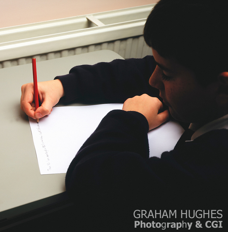 School boy writing in class with pencil.