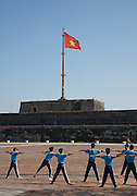 School children exercising below the Vietnamese flag flying on the Flag Tower (Cot Co) Hue Citadel / Imperial City, Hue, Vietnam