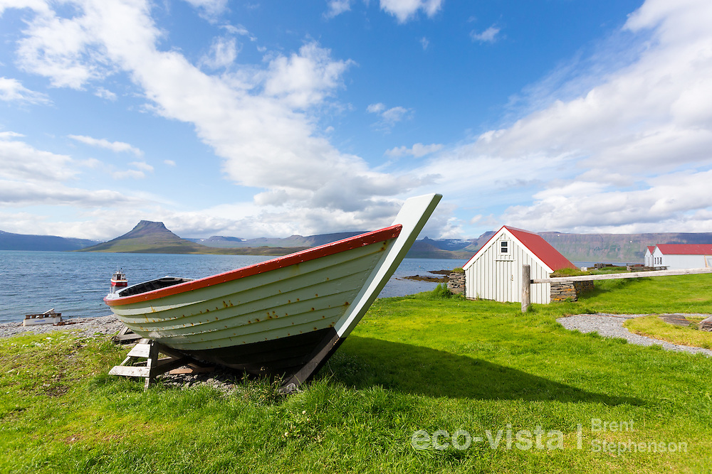 An old wooden row boat lies on the grassy shore beside an old boat house, with the fjord carved by glacial action in the background. Vigur Island, Isafjardardjup, Iceland. July.