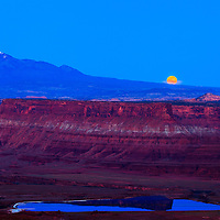 The full moon rises behind the La Sal mountains, over red rock cliffs in the Colorado River Plateau as seen from Dead Horse Point State Park near Moab, Utah.<br />