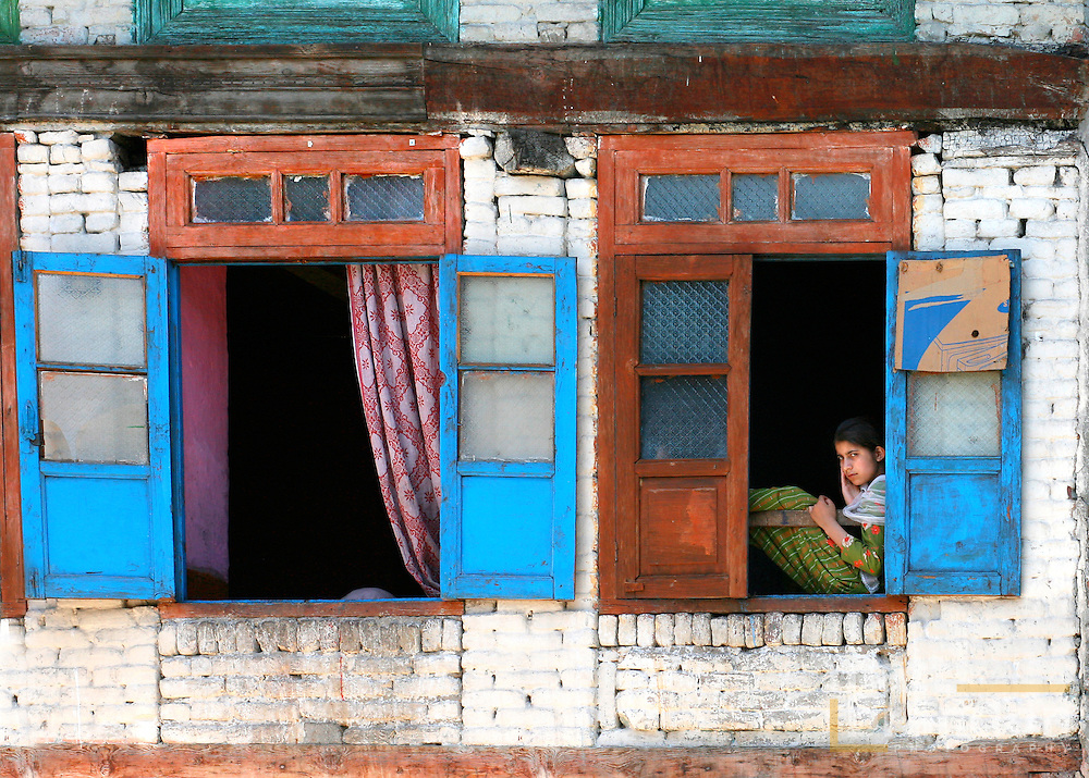 A young girl sits inthe window of her home in rainawari, on Dal lake and watches the world float by.