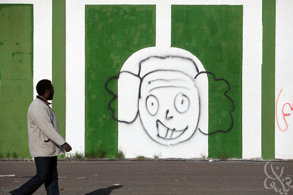 A Libyan man passes a graffiti image of Libyan leader Col. Muammar el-Qaddafi as a clown inside the abandoned and looted Katiba el-Fedeel Boummar military base in Benghazi Libya February 24, 2011. A tightening circle of rebels threatened the capital, Tripoli, on Thursday, as government forces try to fend off an uprising against the 40-year rule of Col. Muammar el-Qaddafi..Slug: Libya.Credit: Scott Nelson for the New York Times