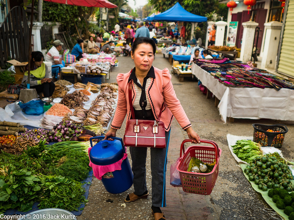 """13 MARCH 2016 - LUANG PRABANG, LAOS: A woman walks through the market in Luang Prabang. Luang Prabang was named a UNESCO World Heritage Site in 1995. The move saved the city's colonial architecture but the explosion of mass tourism has taken a toll on the city's soul. According to one recent study, a small plot of land that sold for $8,000 three years ago now goes for $120,000. Many longtime residents are selling their homes and moving to small developments around the city. The old homes are then converted to guesthouses, restaurants and spas. The city is famous for the morning """"tak bat,"""" or monks' morning alms rounds. Every morning hundreds of Buddhist monks come out before dawn and walk in a silent procession through the city accepting alms from residents. Now, most of the people presenting alms to the monks are tourists, since so many Lao people have moved outside of the city center. About 50,000 people are thought to live in the Luang Prabang area, the city received more than 530,000 tourists in 2014.    PHOTO BY JACK KURTZ"""