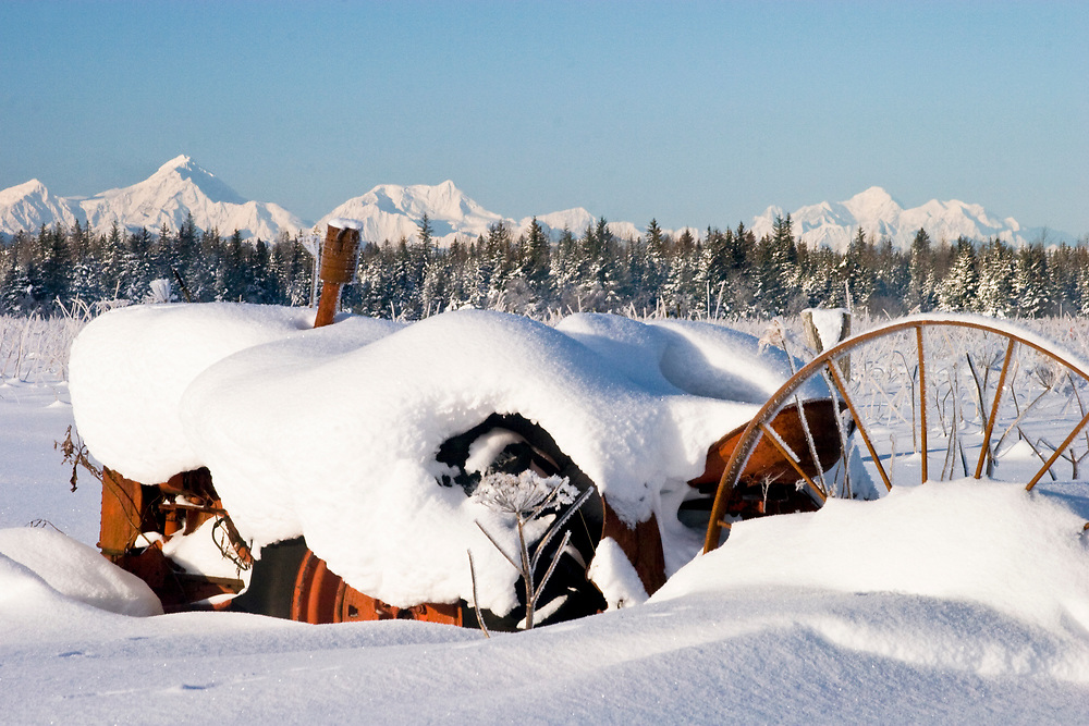 An old, snowy tractor rests in front of the the Fairweather Range (15,320').