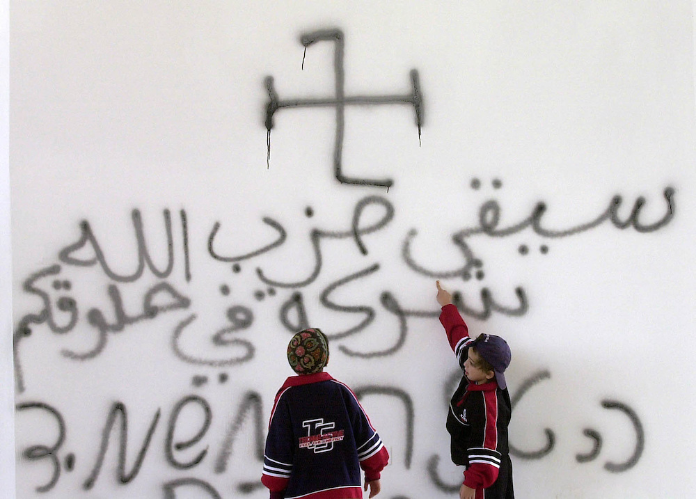 """Children of Jewish settlers point out spray painted swastikas and slogans in Arabic reading """"Hezbollah will stick in your throat like a bone""""and in Hebrew reading """"Hitler destroys the germs"""", written by suspected Palestinian intruders that vandalized the main synagogue of the West Bank Jewish settlement of Erfrat Friday Oct. 27, 2000."""