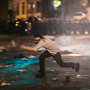 WASHINGTON, USA - APRIL 27: A rioter runs for cover as police fire non-lethal rounds at him during riots in Baltimore, USA on April 27, 2015. Protests following the death of Freddie Gray from injuries suffered while in police custody have turned violent with people throwing debris at police and media and burning cars and businesses.
