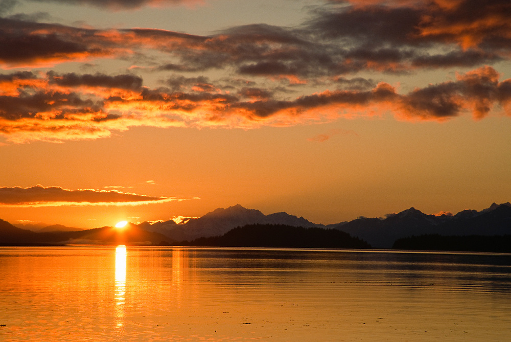 Alaska. Glacier Bay NP. Sunset light spilling onto the Beardslee Islands. The calm ocean waters of the Inside Passage in Southeast Alaska.