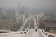 A man ascending an arch of Lupu Bridge over the Huangpu River. Shanghai, China, 2007