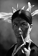 A female member of the Laytu Chin tribe, who traditionally tatoo the faces of their women, smoking a pipe in her village near Mindat, Myanmar (Burma).