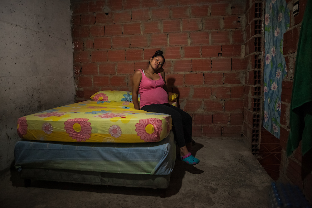 Marisol de los Angeles Becerra, 20, is preganant with her first child, who she will name David Alejandro.  Her husband works as a motorcyle-taxi driver and they have lived at the tower for three and a half years.  She lives on 28th floor, the very top inhabited floor of the tower.  She worked as a shoe seller, and was paid a minimum salary plus 2 dollars for every pair of shoes she sold, but since becoming pregnant she has hardly made the trip down the 28 flights of stairs, because there are not elevators inside the tower. She likes to sit on the terrace and watch the stars and lights of the city at night. PHOTO: Miguel Gutierrez